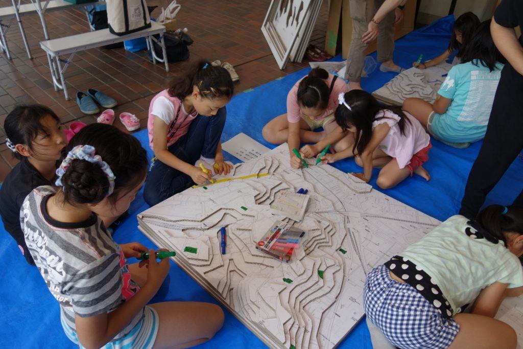 マンション周辺を再現した段ボールジオラマに、カラーペンで色を付けていく子どもたち